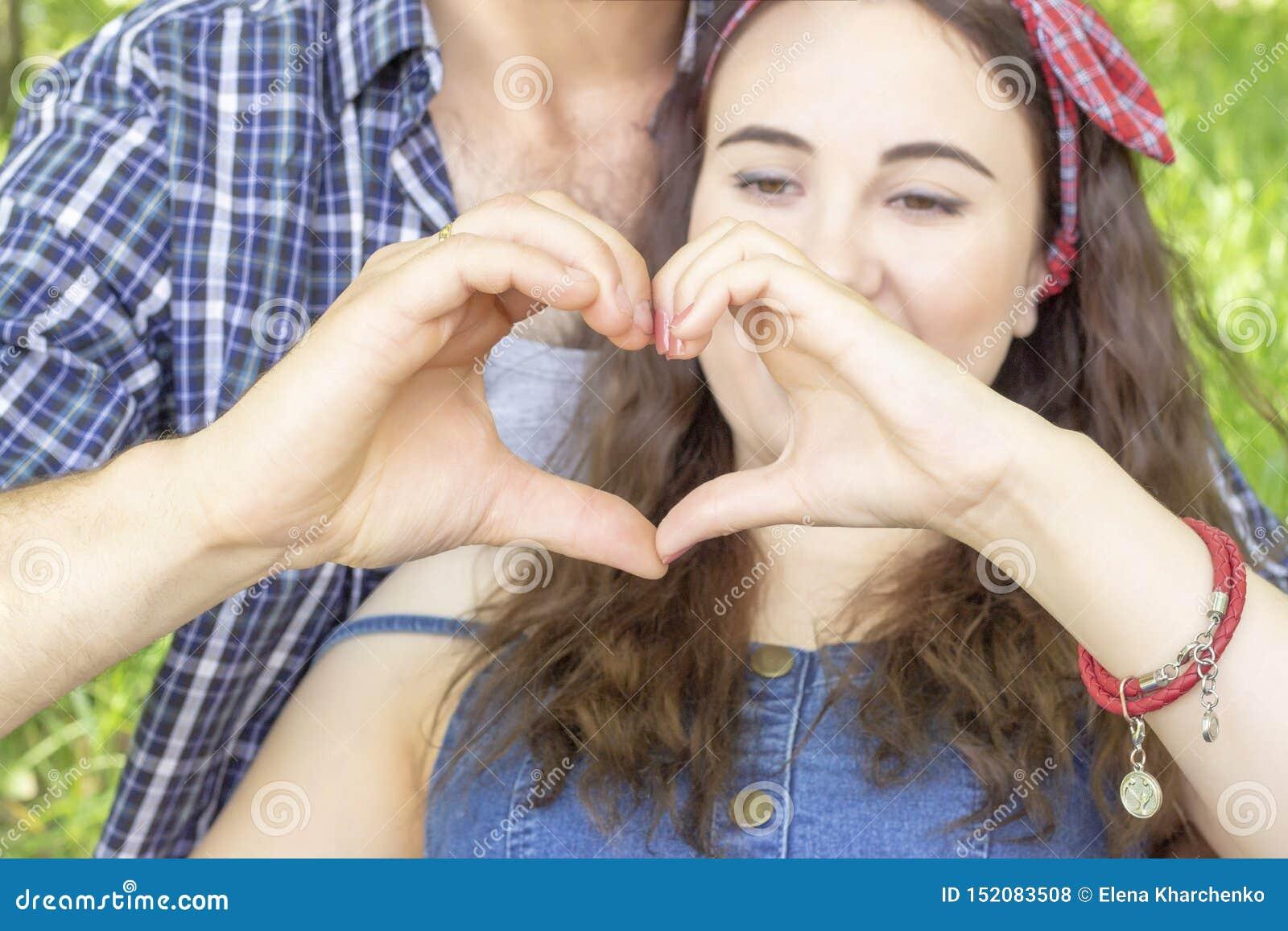 做心脏用手的年轻夫妇 遇见爱夏天野餐