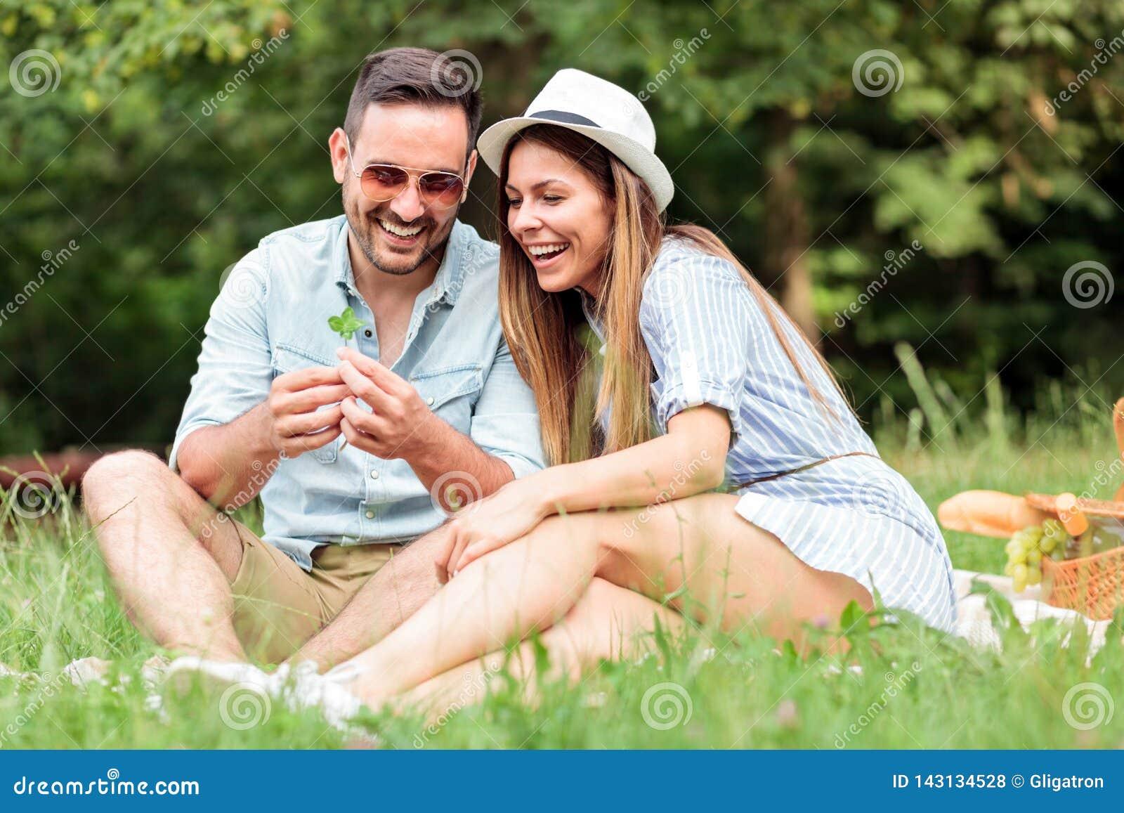 做愿望的美好的年轻夫妇在发现四片叶子三叶草以后