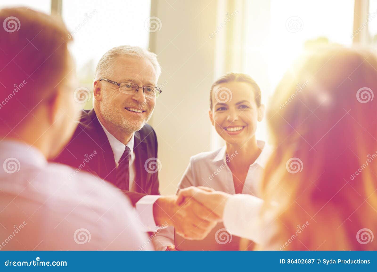 做握手的资深商人在办公室