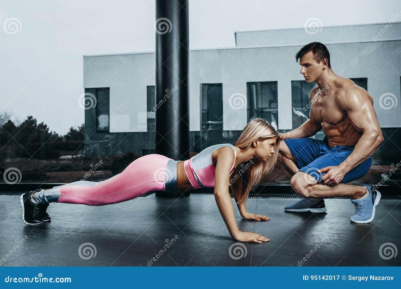 做板条锻炼训练和有教练员的嬉戏妇女新闻肌肉 体育健身锻炼力量力量