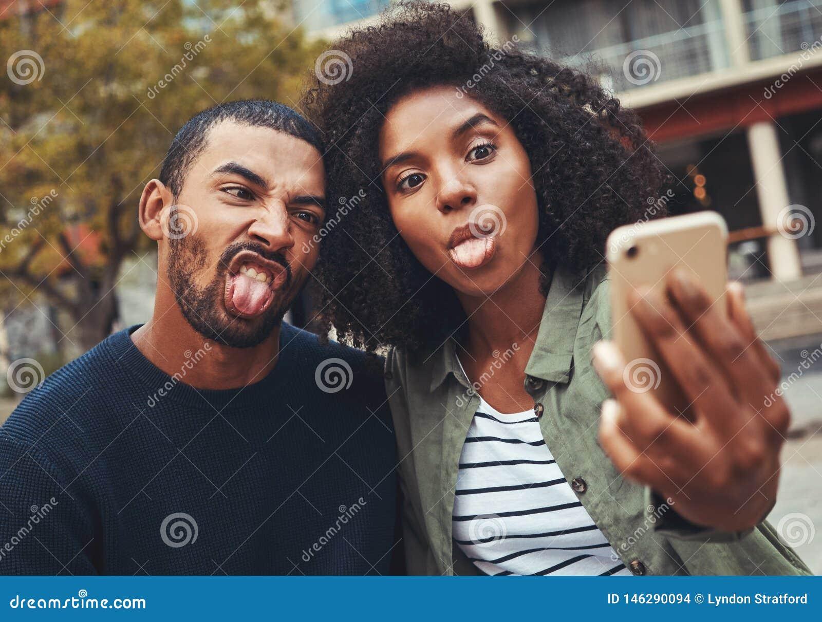 做滑稽的面孔的年轻夫妇,当采取selfie在智能手机时