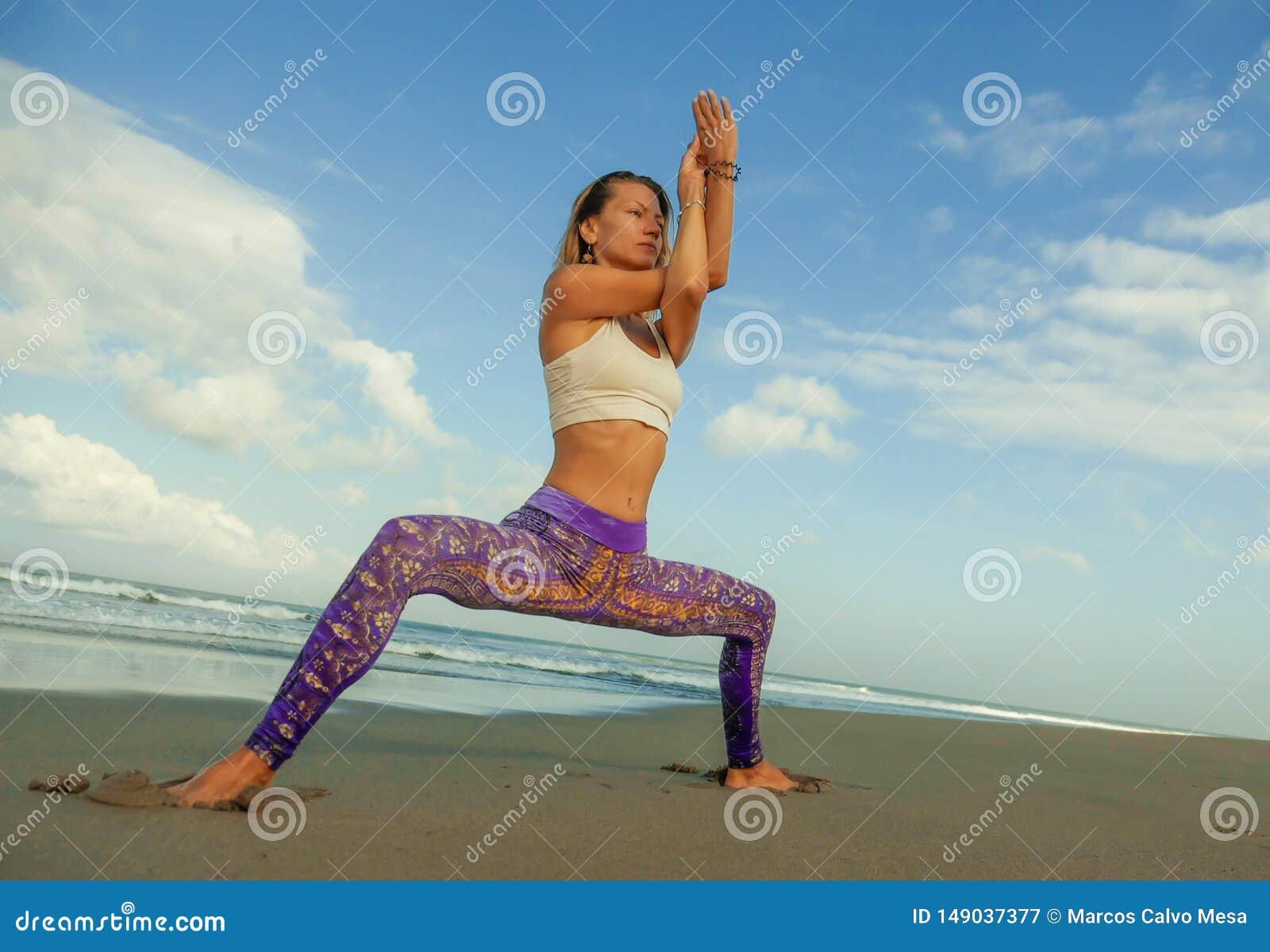 做瑜伽和放松锻炼的年轻愉快和有吸引力的适合和亭亭玉立的白肤金发的妇女自然生活方式画象户外在