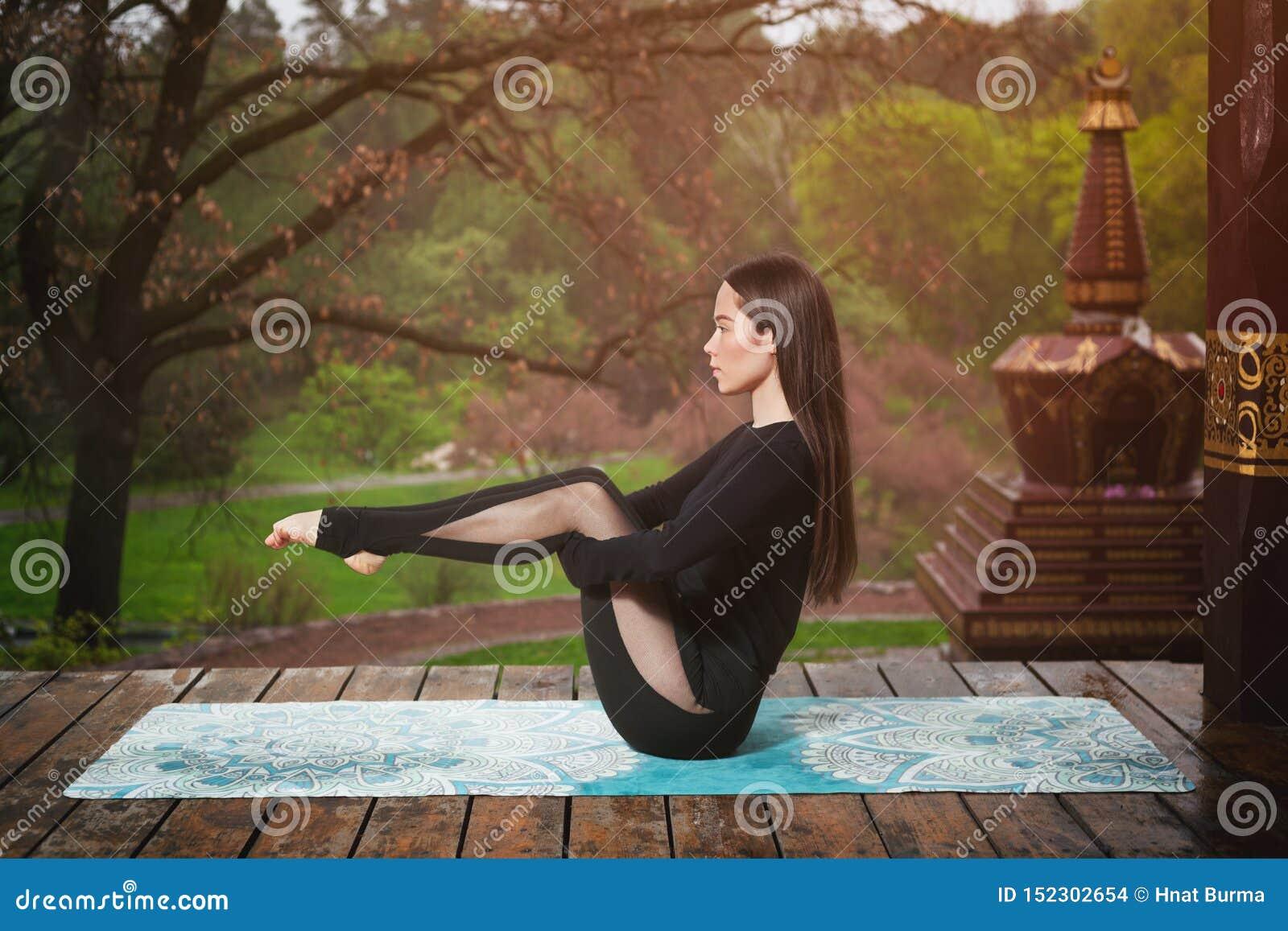 做瑜伽锻炼的年轻女人户外 瑜伽凝思在公园