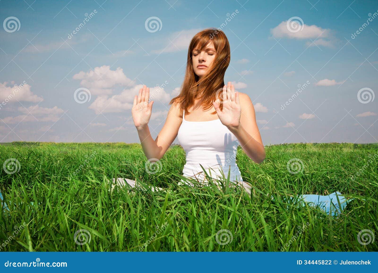 做瑜伽(蓮花姿勢)的女孩在公園圖片