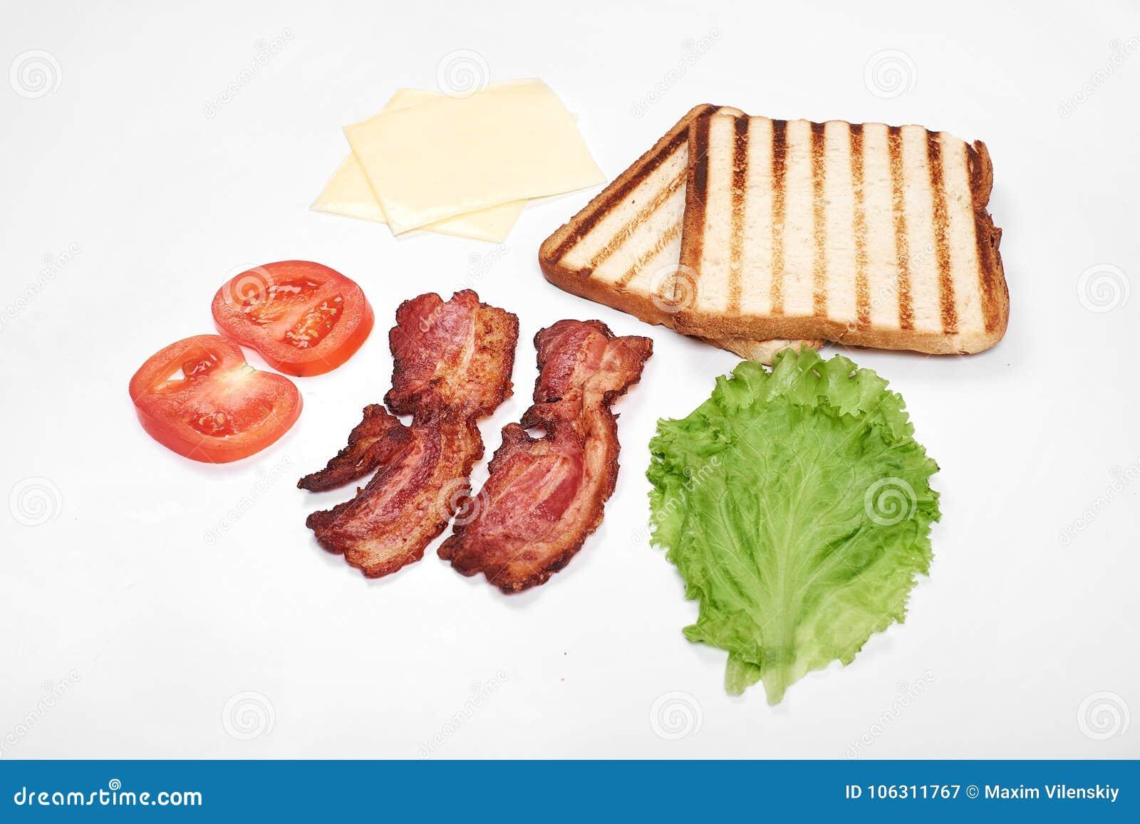 做的三明治成份 新鲜蔬菜,蕃茄,面包, becon,乳酪 隔绝在白色背景,上面