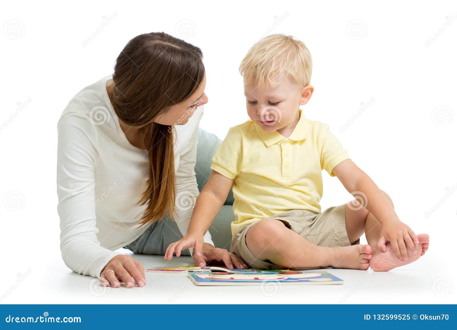做的母亲演奏难题玩具与她的在白色背景隔绝的地板上的孩子儿子一起
