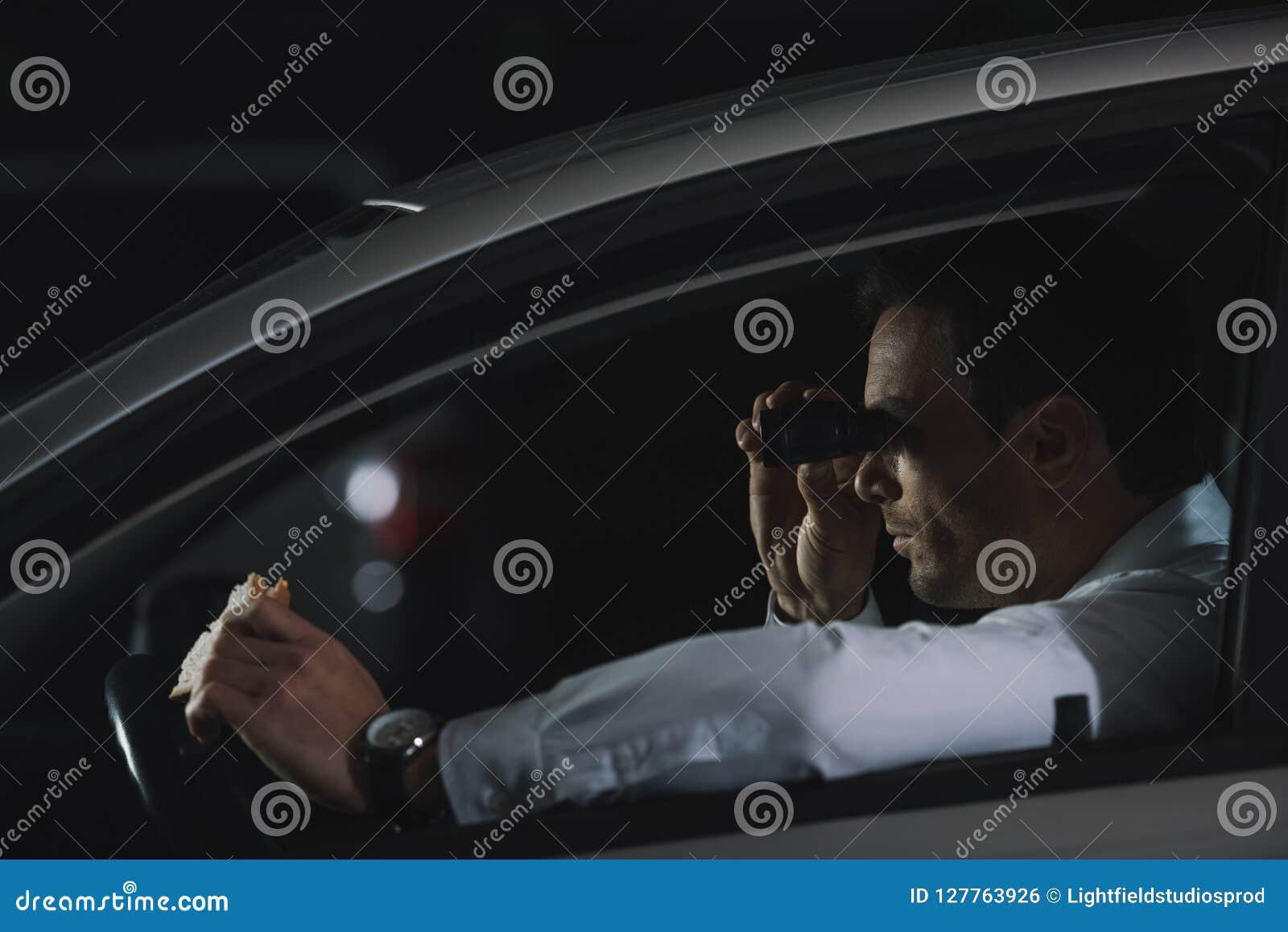 做监视由双筒望远镜和吃三明治的暗中进行的男性代理侧视图