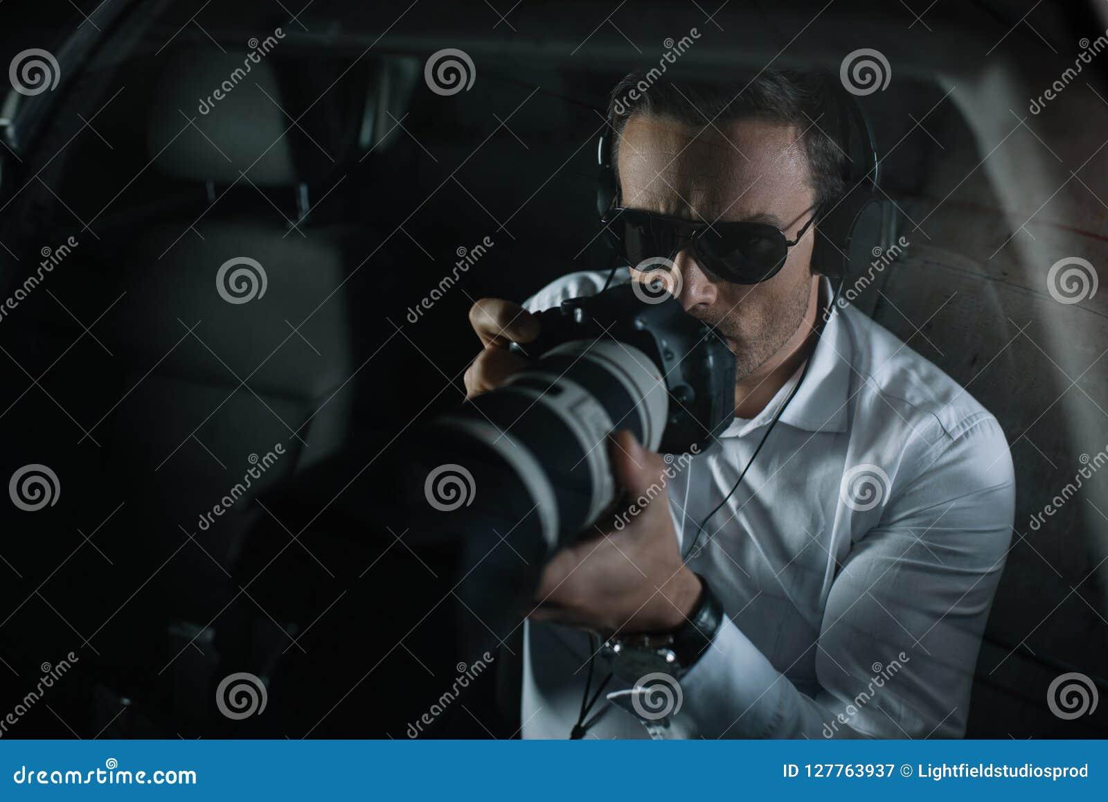 做监视的耳机的男性私家侦探由与接物镜的照相机