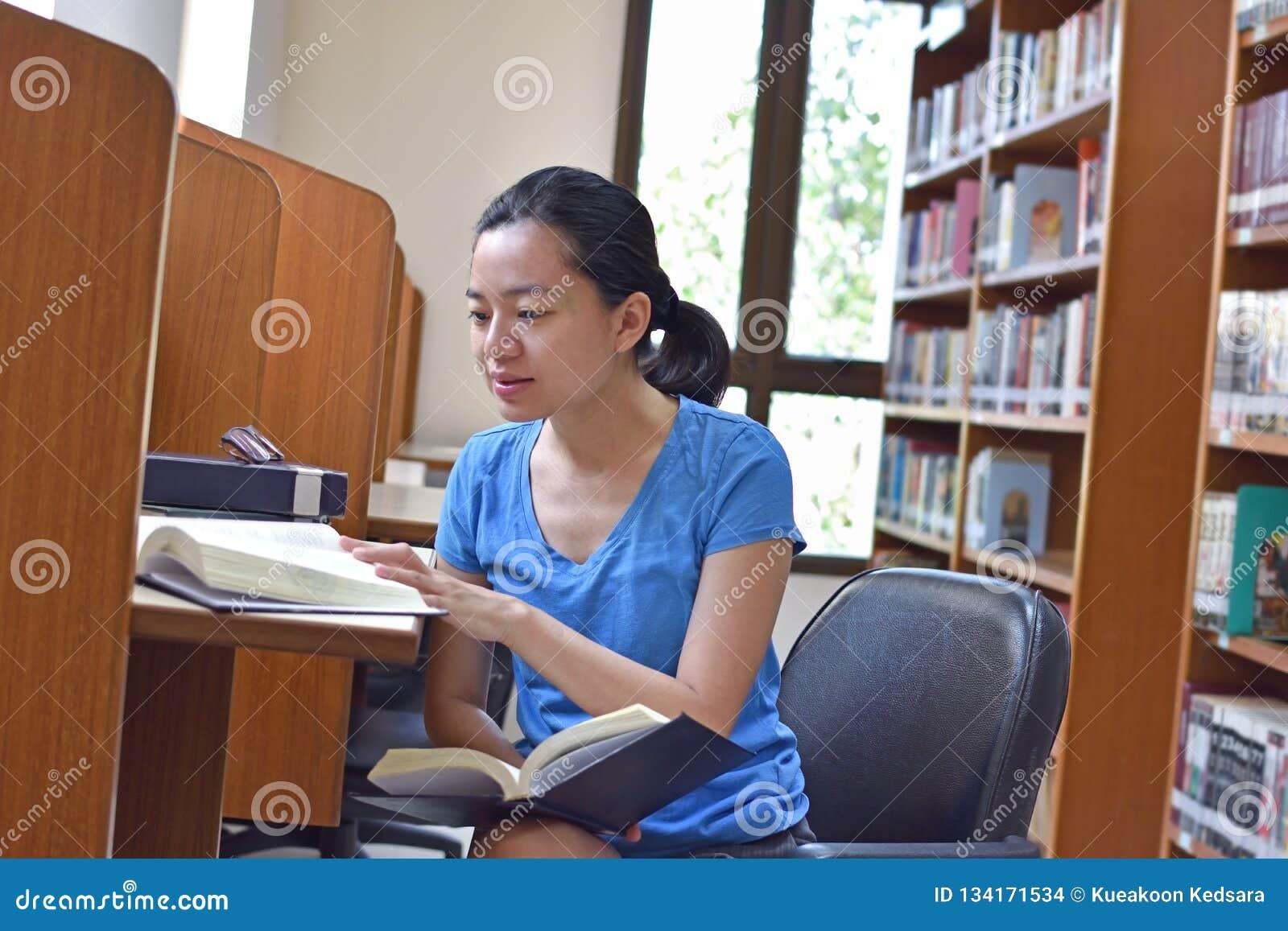 做研究和看书的亚裔妇女在图书馆里
