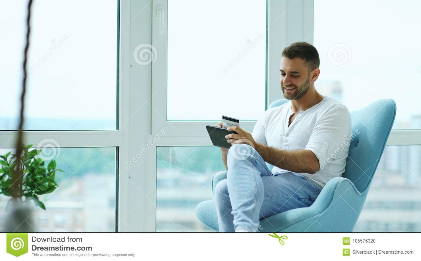 做网上购物的年轻微笑的人使用坐在现代顶楼公寓的阳台的数字式片剂计算机
