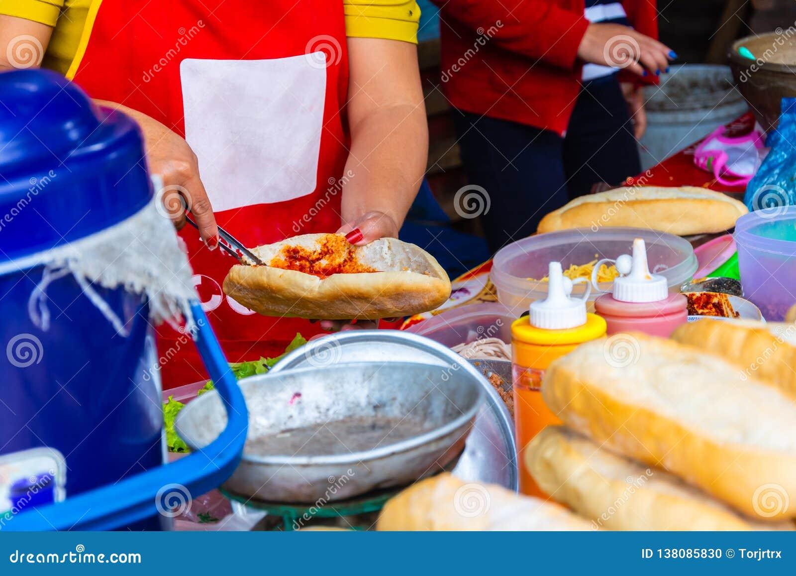 做老挝样式长方形宝石或法式面包sanwich,高度普遍的早餐街道食物的女性厨师在老挝