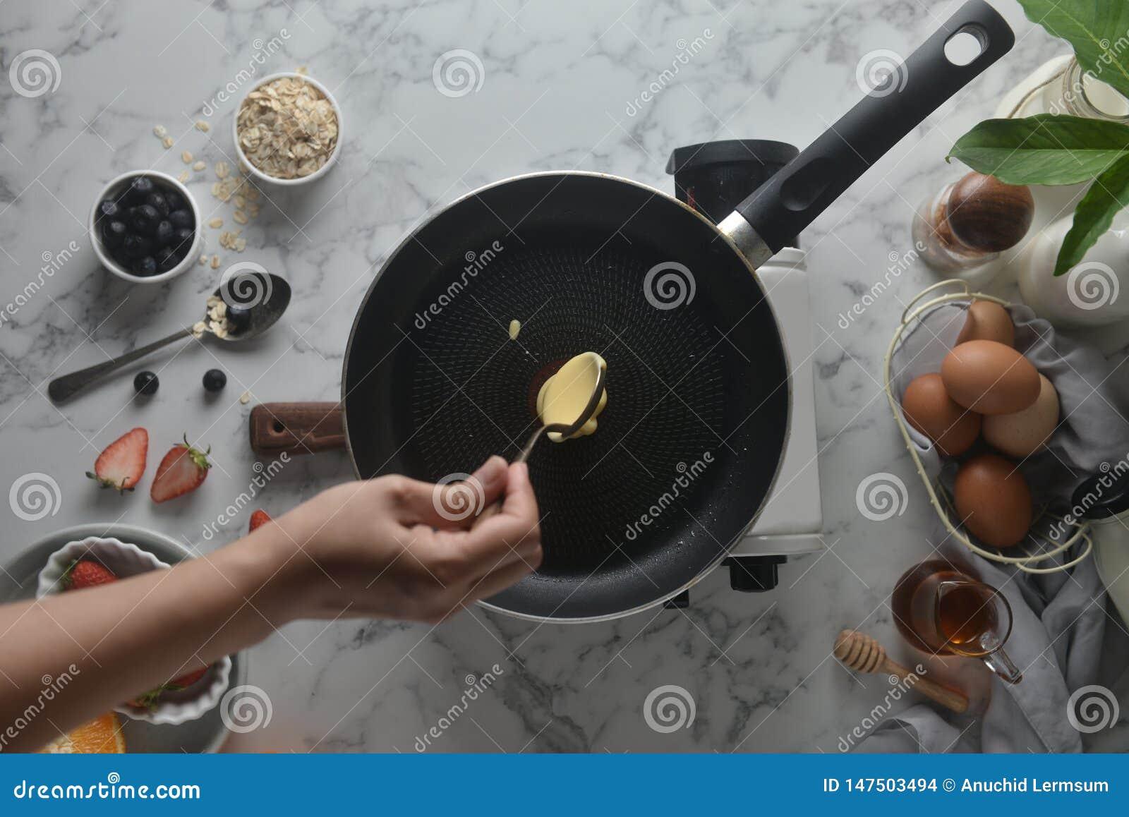 做薄煎饼,蛋糕,面包师的手烘烤的顶视图倾吐或挖出在平底锅上的面团 烹调成份的概念和