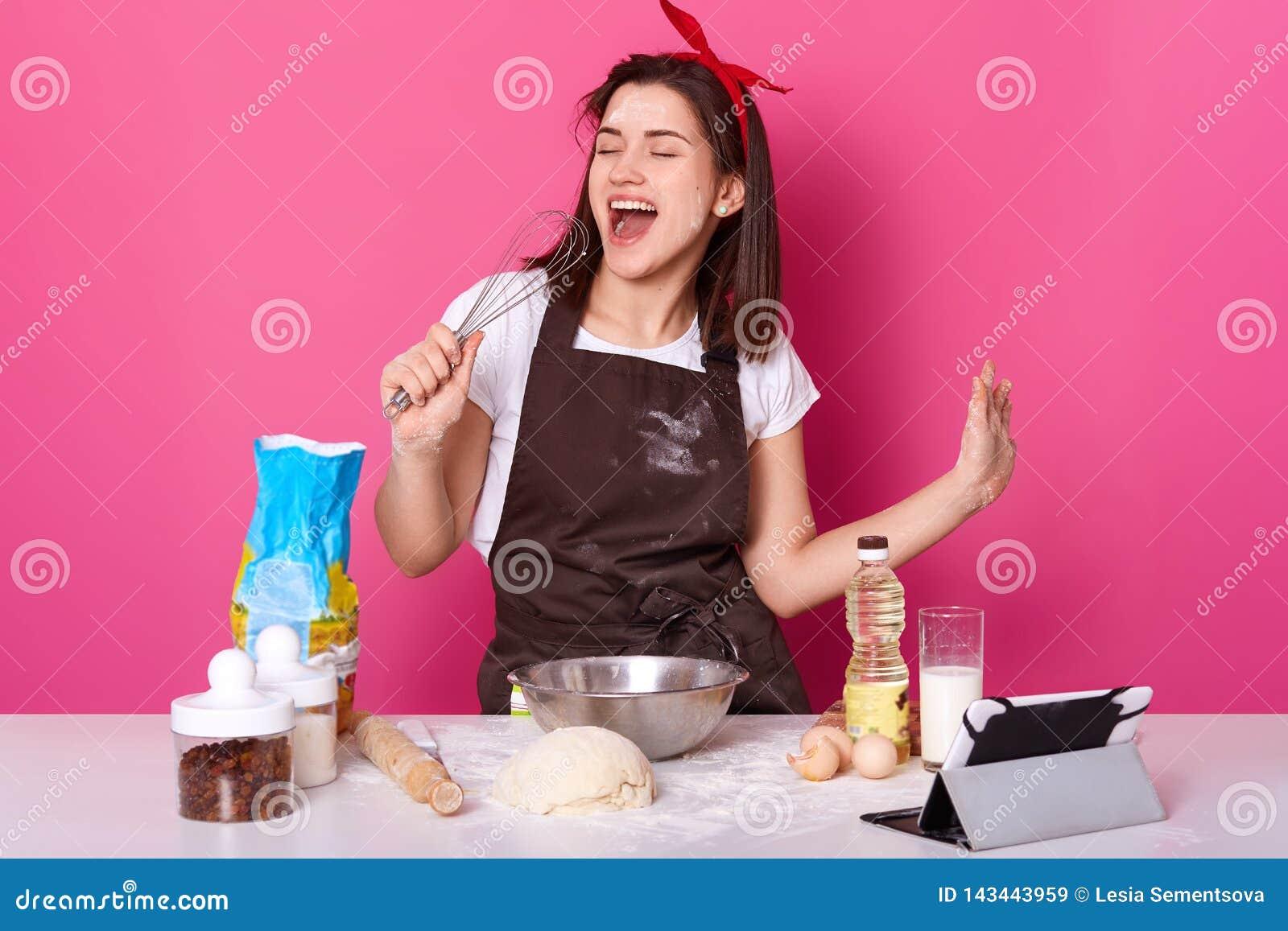 做蛋糕的美女照片 夫人站立在玫瑰色墙壁,拿着飞奔作为话筒并且唱歌曲,听的音乐一会儿