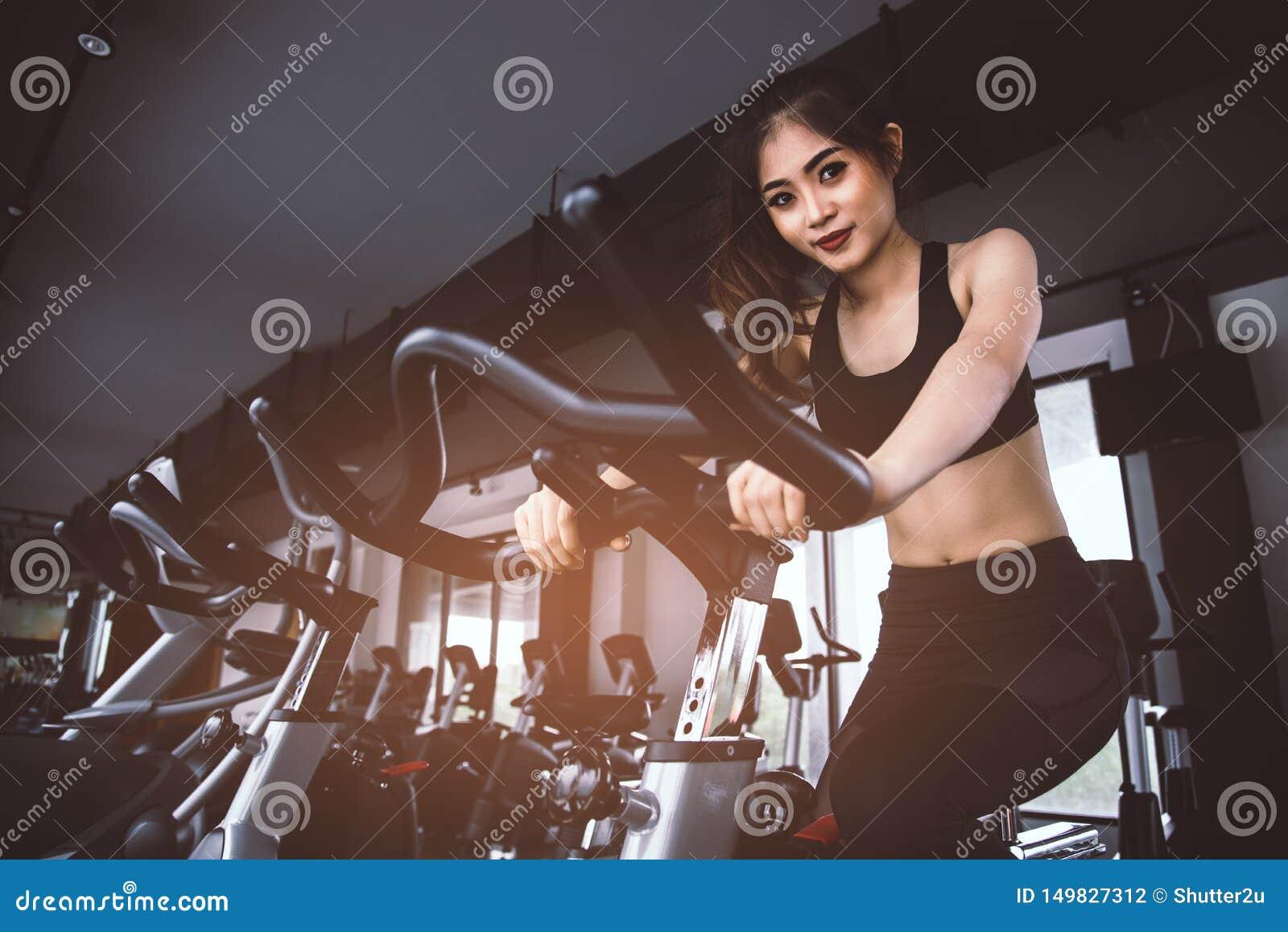 做转动在健身房的自行车的亚裔健身妇女 美丽的年轻女性在健身房自行车解决 医疗和健康概念