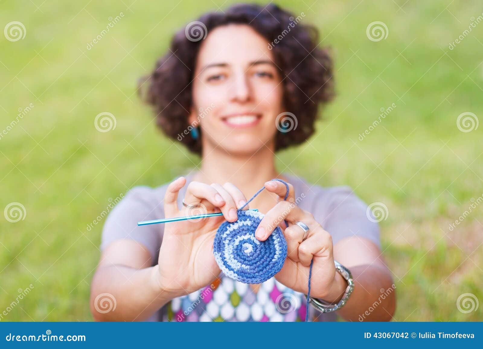 做钩针编织握持热锅的布垫子的愉快的微笑的妇女户外