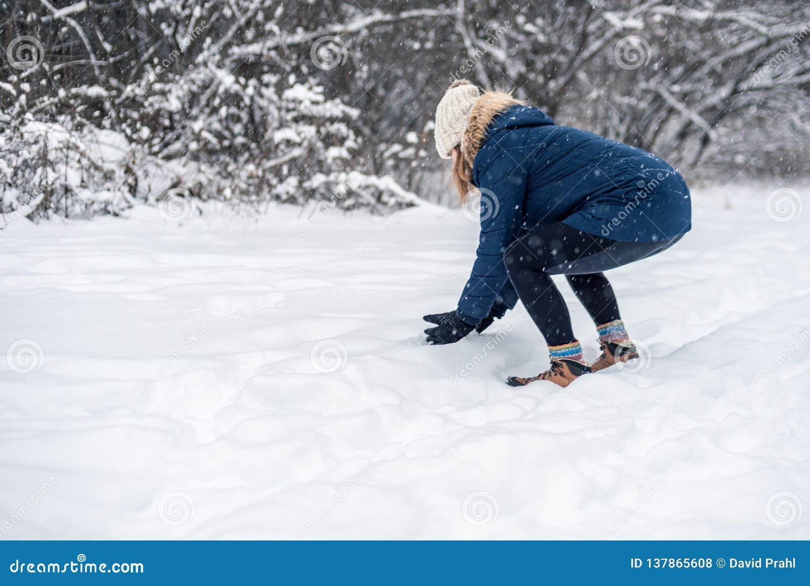 做雪球的年轻女人外面在一多雪的天