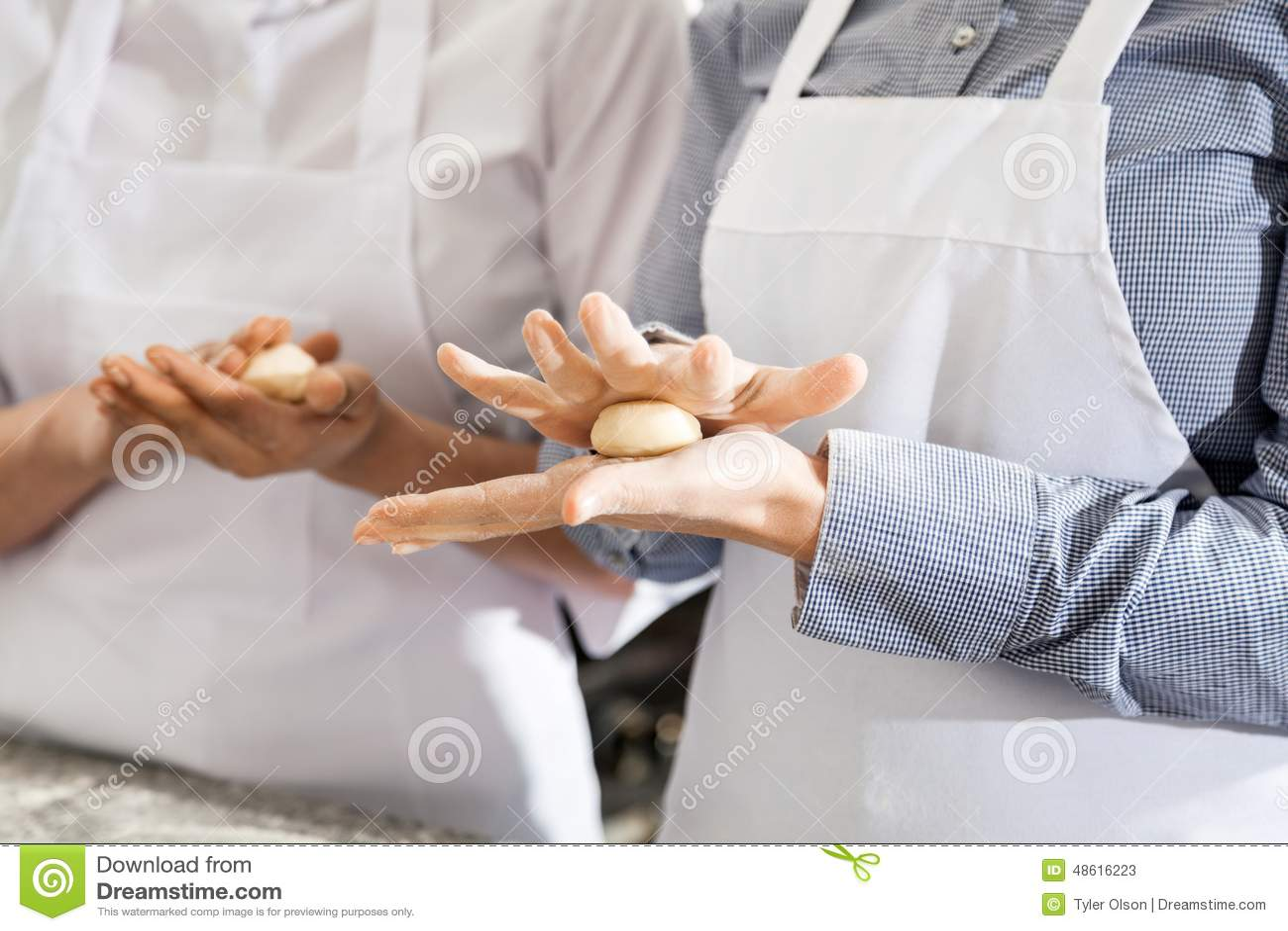 做面团面团球的女性厨师在厨房里