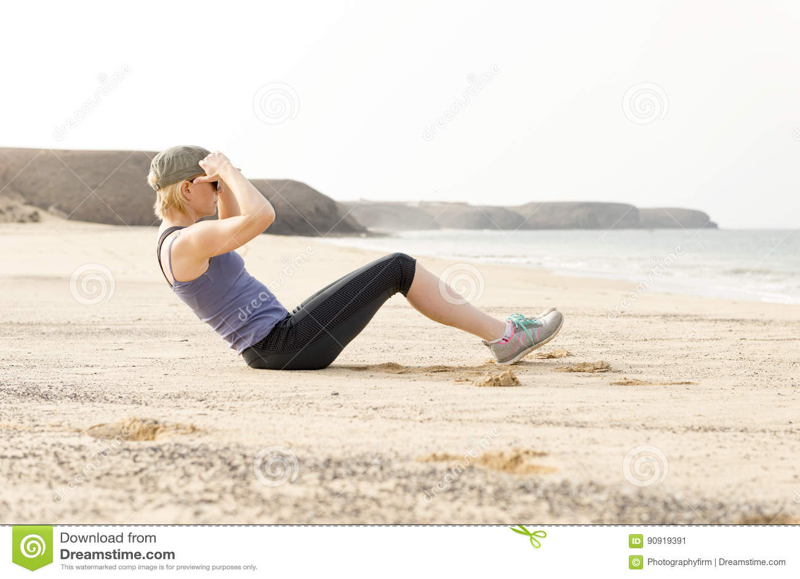 做仰卧起坐的活跃妇女由海滩