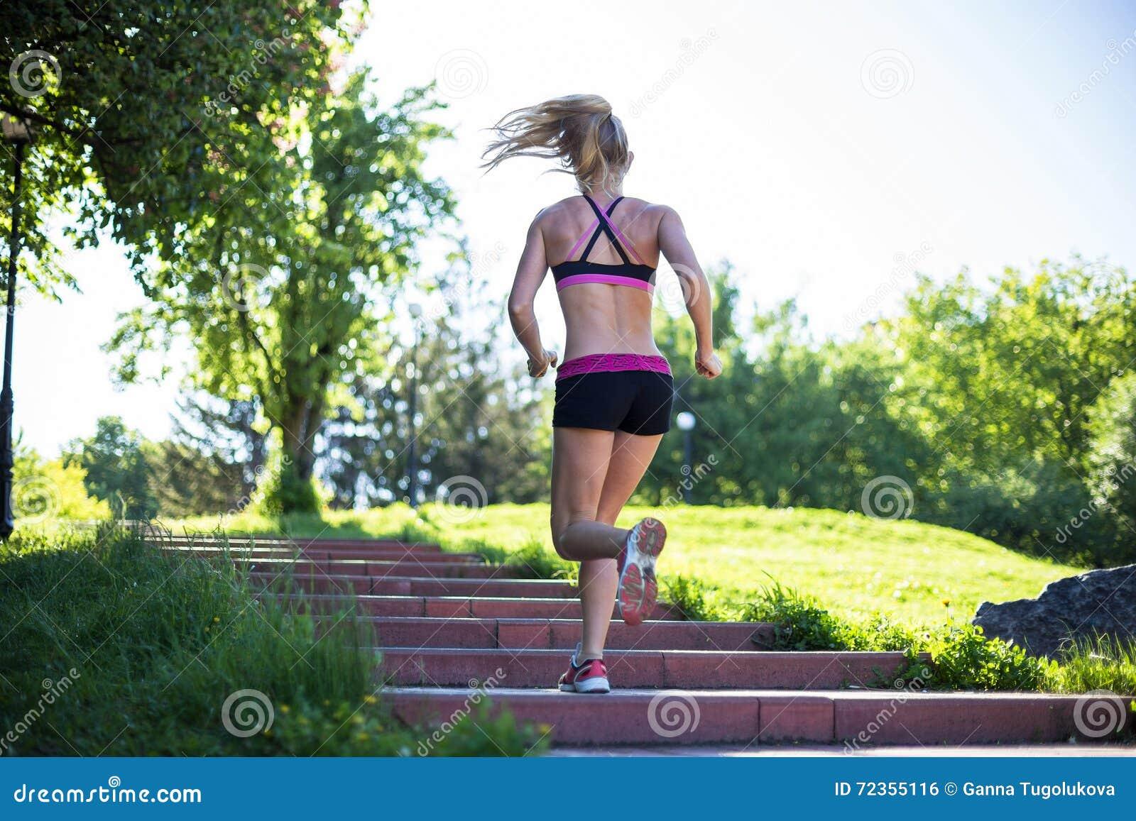 做锻炼的健身妇女在室外交叉训练锻炼期间在晴朗的早晨
