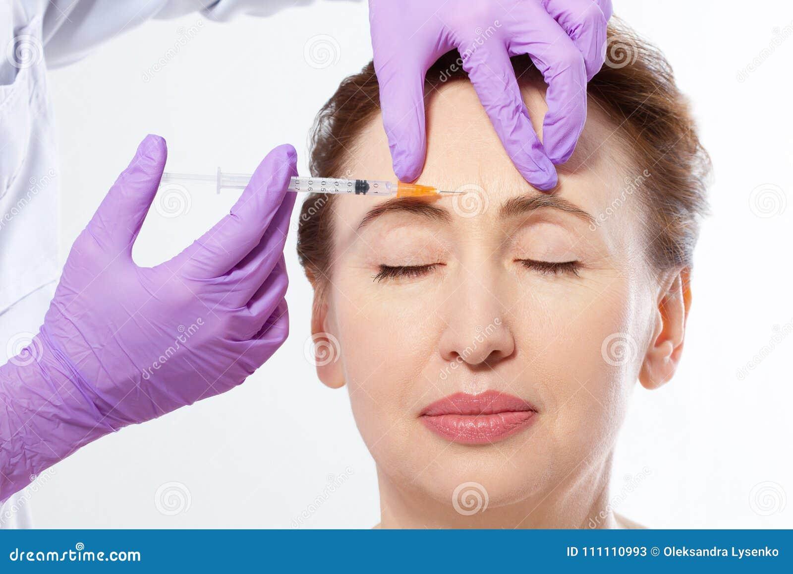 做botox射入的一名美丽的中年妇女和医生手的特写镜头画象被隔绝在白色背景 胶原