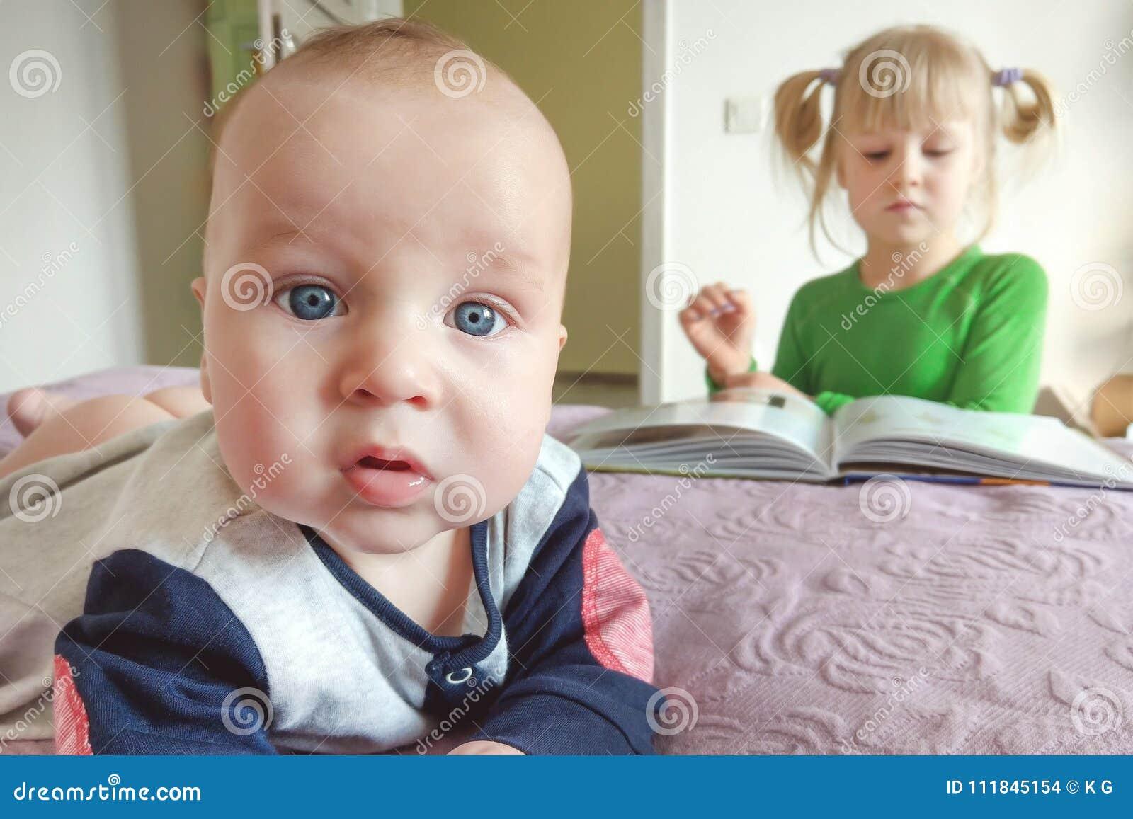 做selfie的沉思矮小的婴儿男孩画象在床 姐妹在背景的阅读书 浓缩的年龄的不同的兴趣