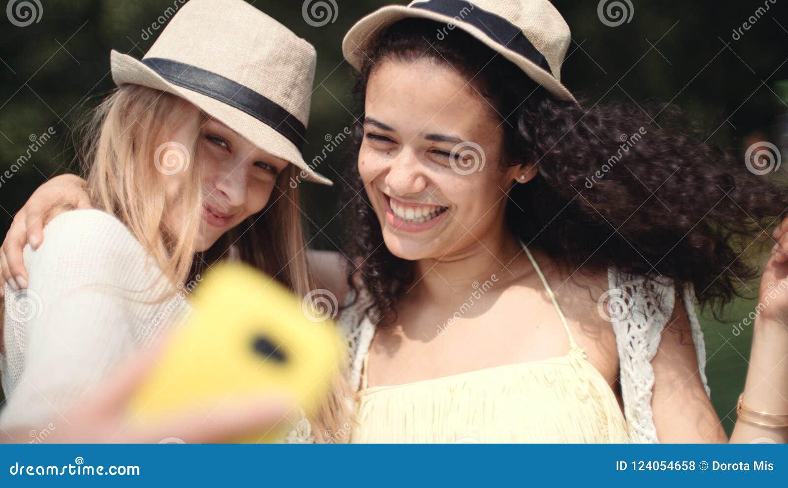 做selfies的两个快乐的女孩由湖