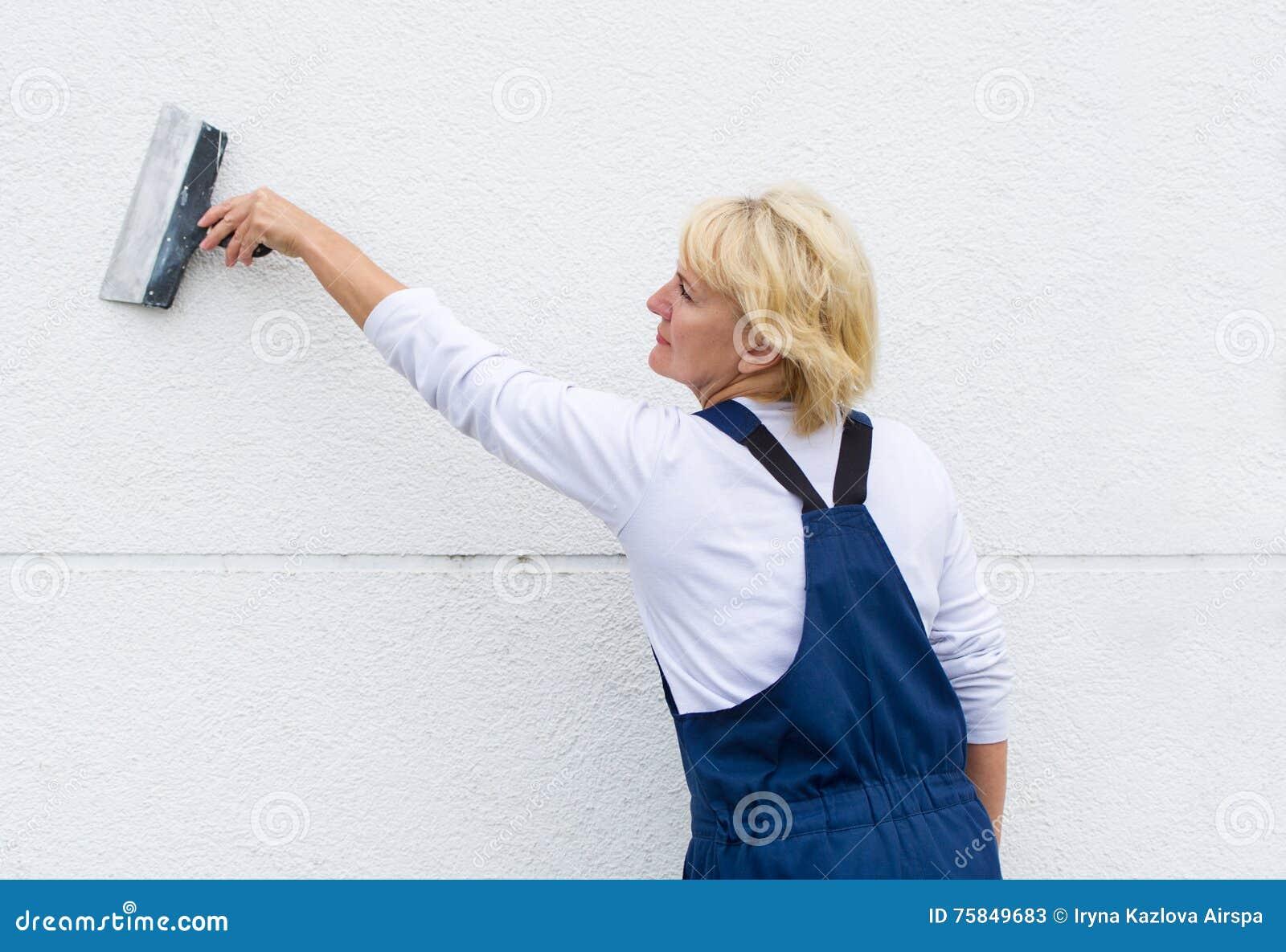 停止与小铲的室外墙壁整修的女工