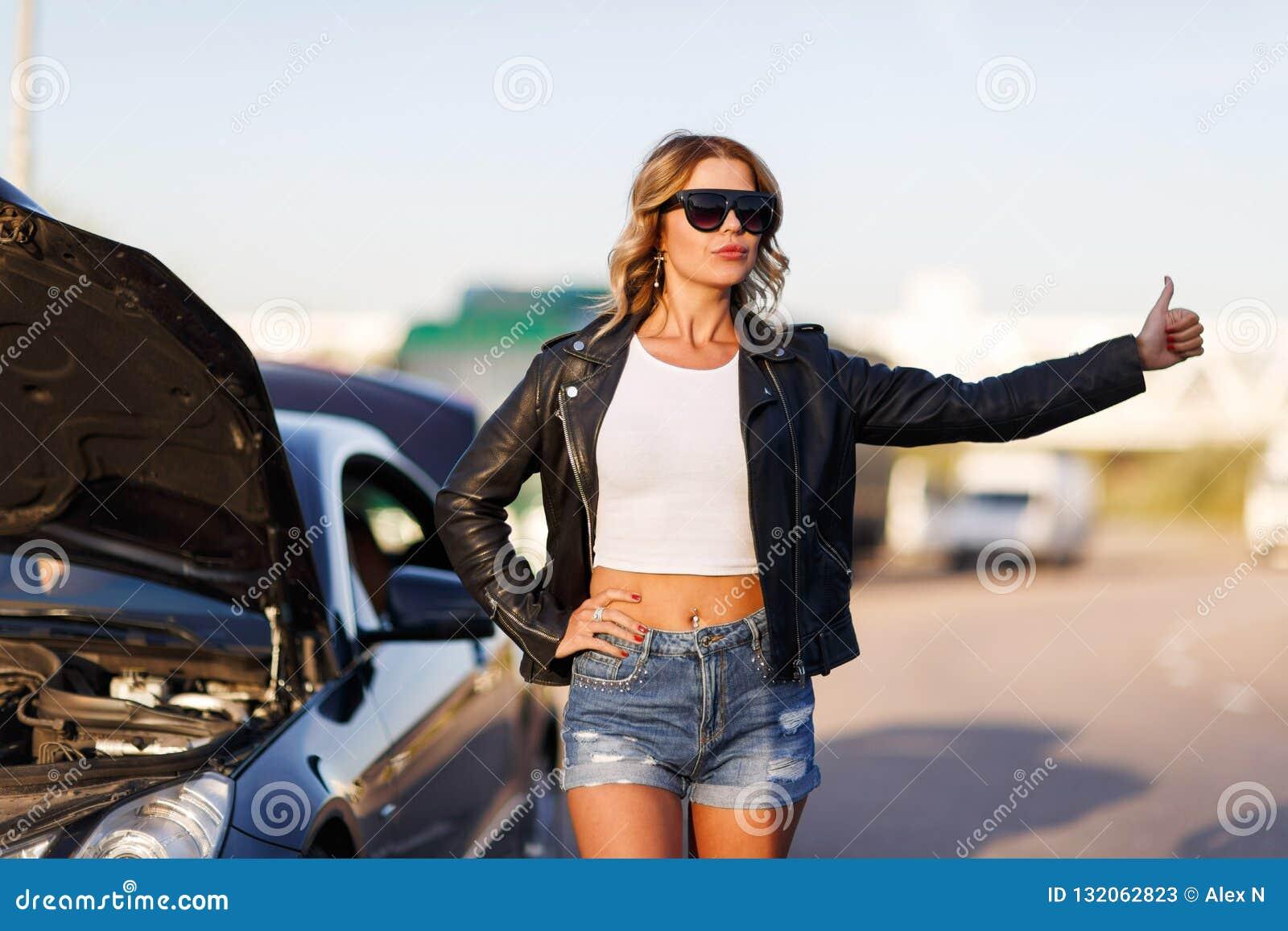 停止在街道上的年轻白肤金发的女孩的图片汽车