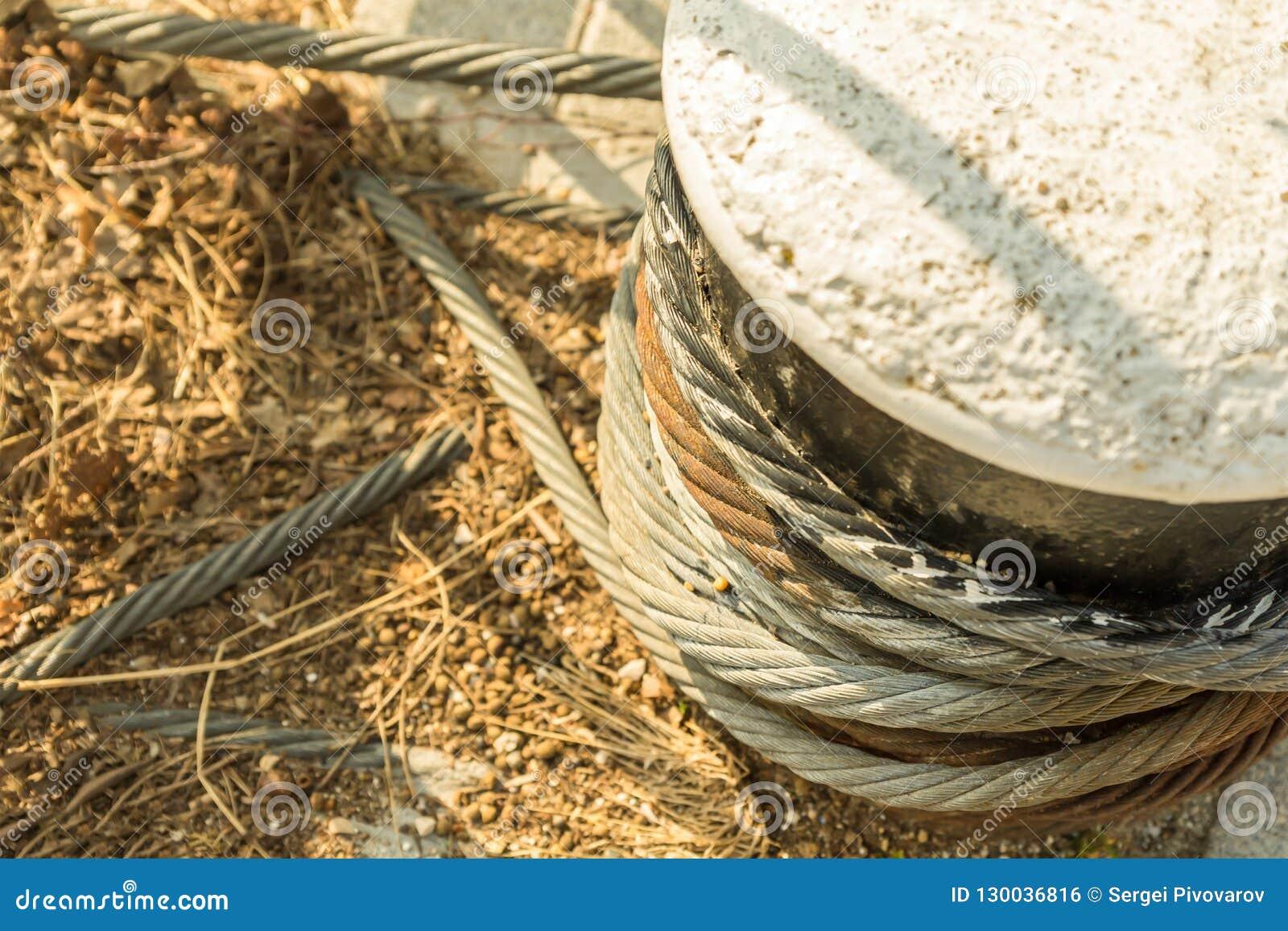 停泊在水泥块固定的一部分的港设备粗糙的扭转的绳索铁生锈的被风化的特写镜头