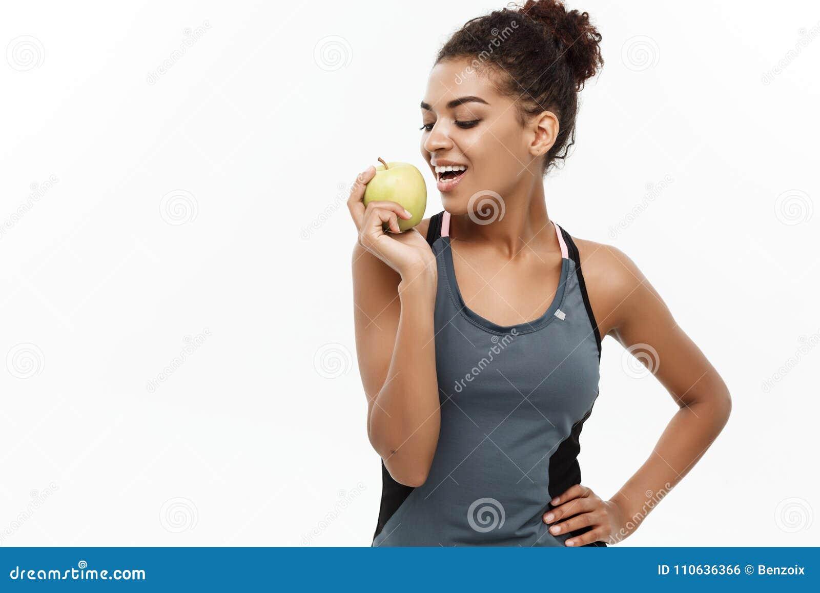 健康和健身概念-灰色健身的美丽的美国非洲夫人给吃绿色苹果穿衣 隔绝