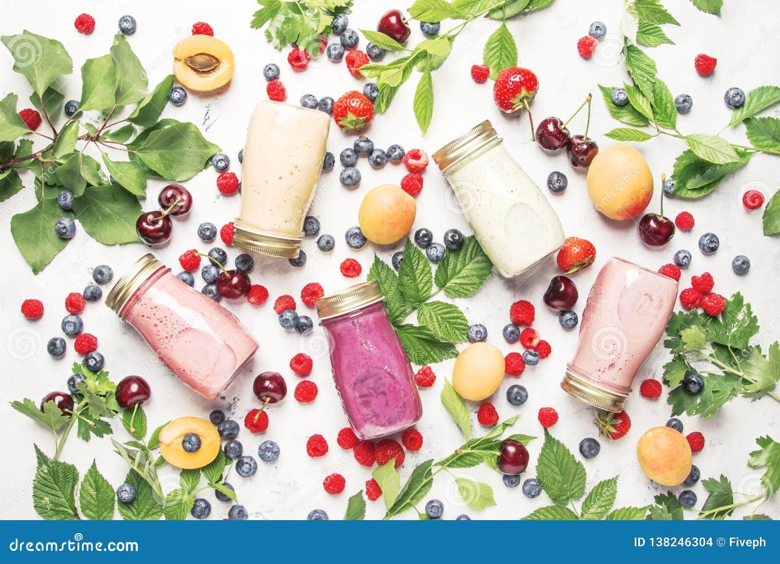 健康和有用的五颜六色的莓果cokctalis、圆滑的人和奶昔用酸奶,新鲜水果和莓果在灰色桌,顶视图上