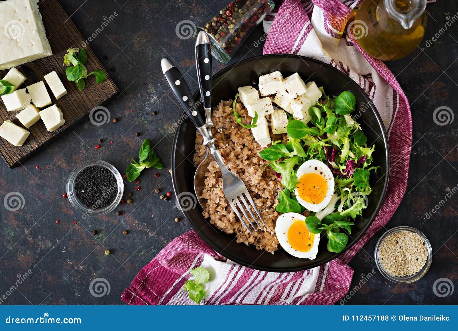 健康早餐用在黑暗的背景的蛋、乳酪、莴苣和荞麦粥 适当的营养 饮食菜单
