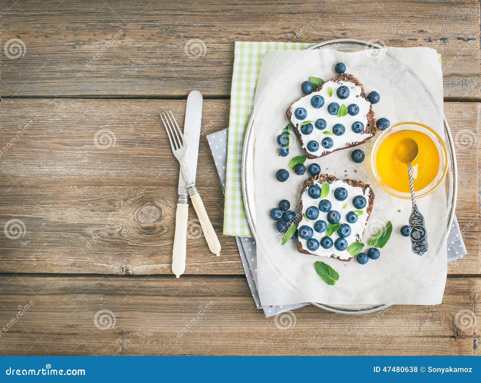 健康早餐设置了与乳清干酪,新鲜的蓝莓,蜂蜜和