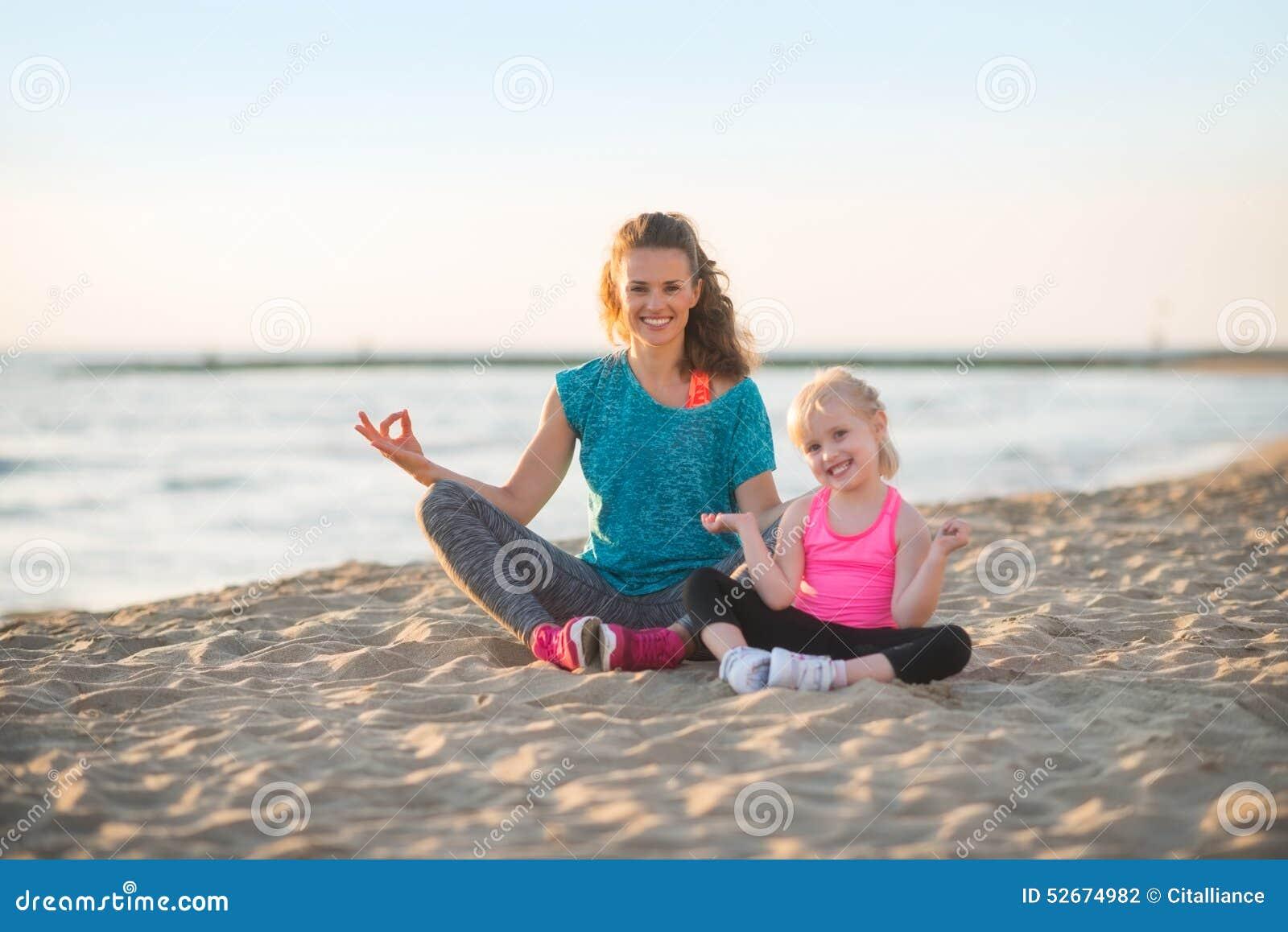 健康母亲和做在海滩的女婴瑜伽