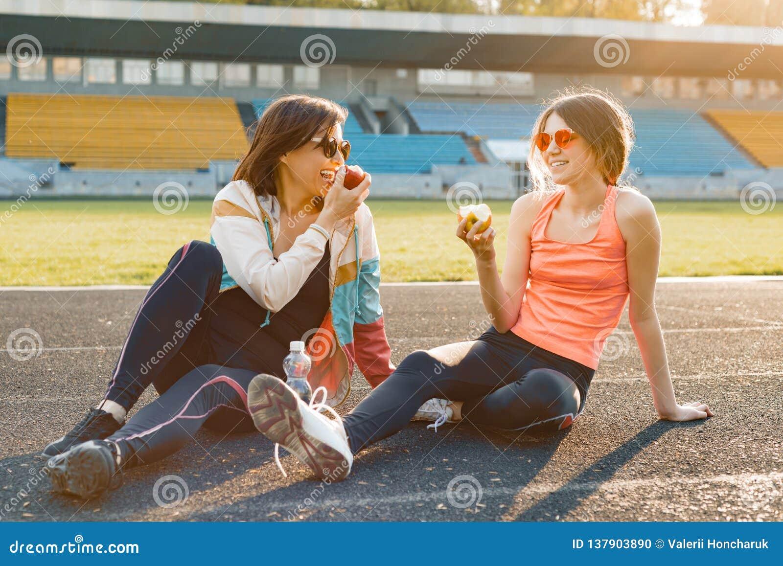 健康生活方式和健康食物概念 一起吃在体育场的微笑的健身母亲和青少年女儿苹果开会