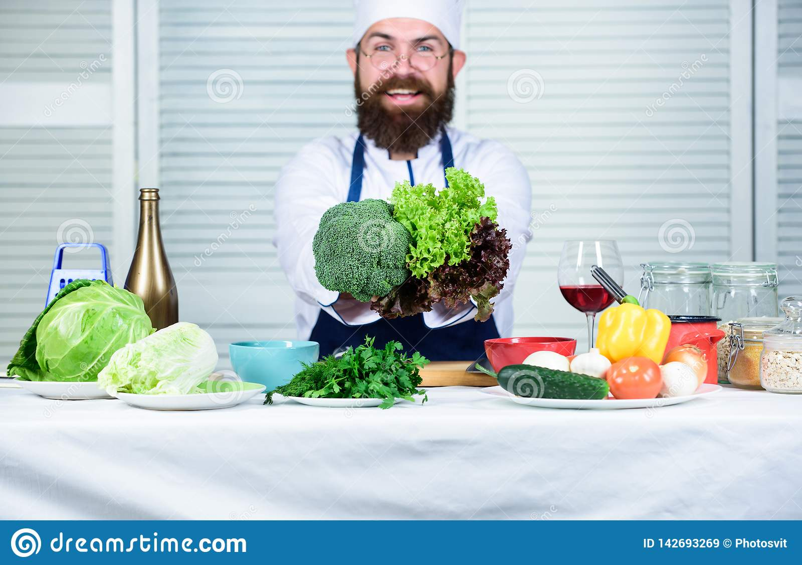 健康素食食谱 人厨师帽子和围裙举行硬花甘蓝 有机蔬菜 概念健康营养 博若莱红葡萄酒