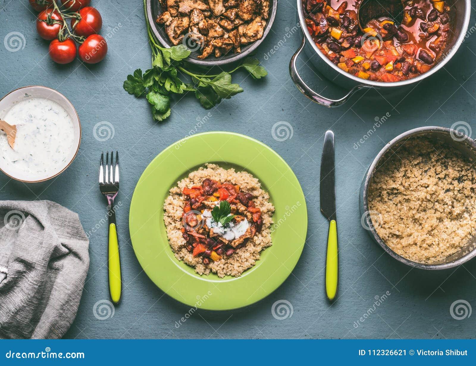 健康膳食用奎奴亚藜,蕃茄豆调味和在厨房用桌背景的炸鸡肉