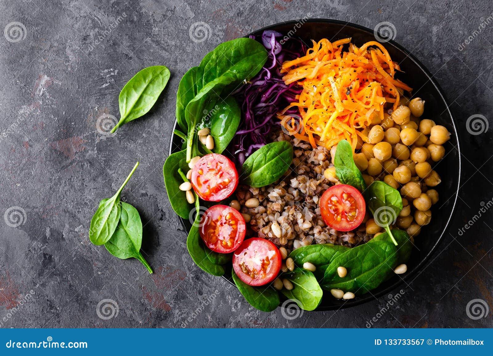 健康蔬菜菜肴用荞麦和鸡豆、无头甘蓝、红萝卜、新鲜的蕃茄、菠菜叶子和松果菜沙拉