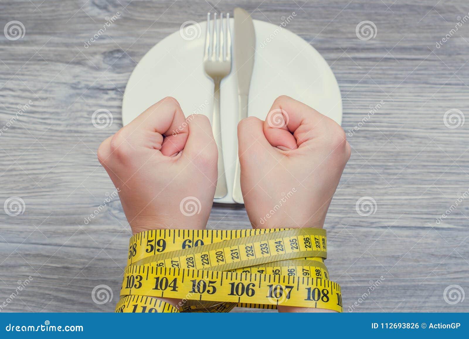 健康身体关心不健康吃节食的饿减重减肥 坏食物habbits和不健康吃的概念 妇女`