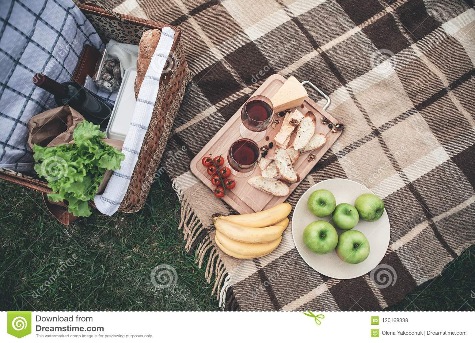 健康食物和葡萄酒杯在草浪漫野餐的