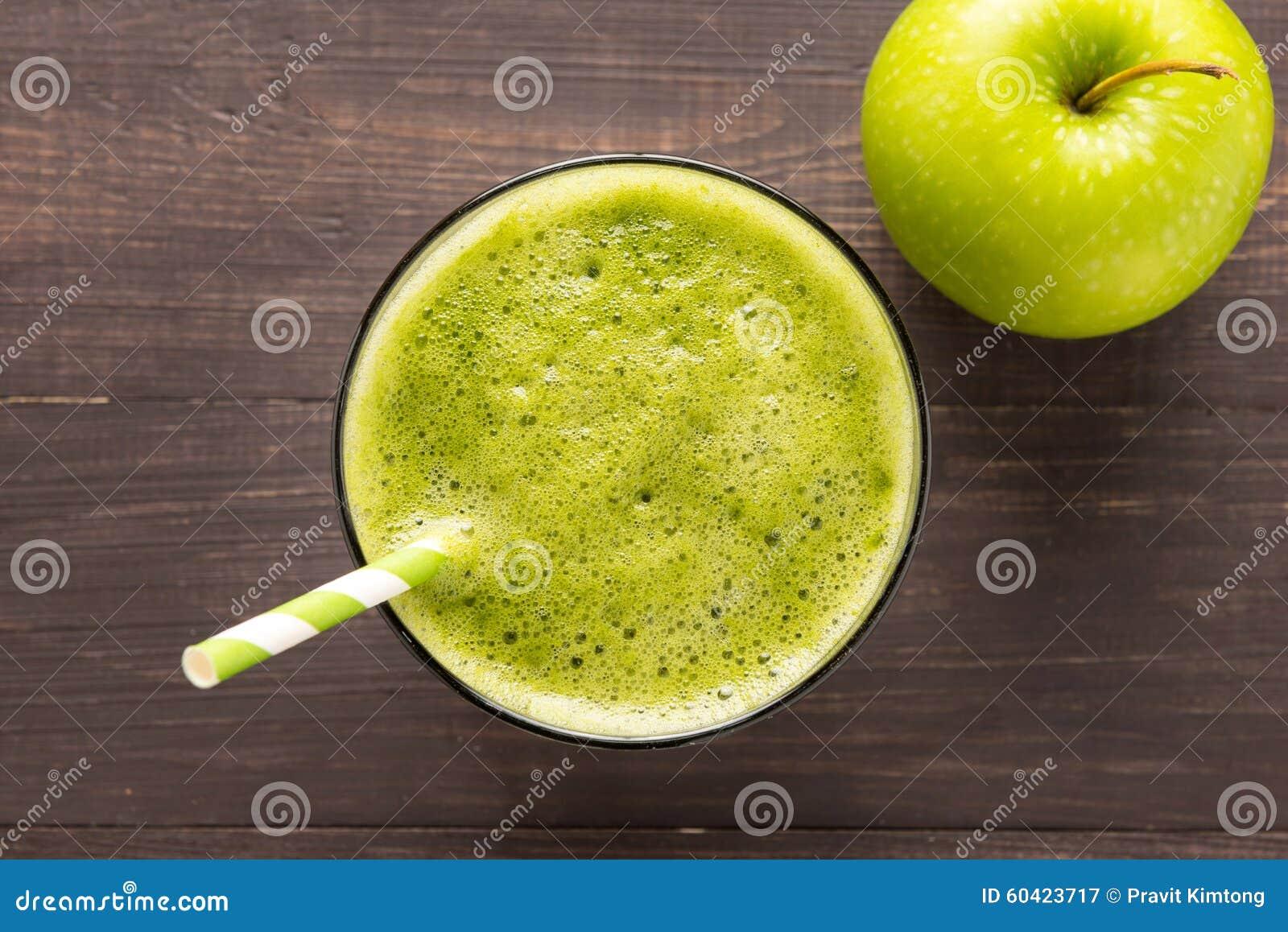 健康绿色圆滑的人用在土气木背景的苹果