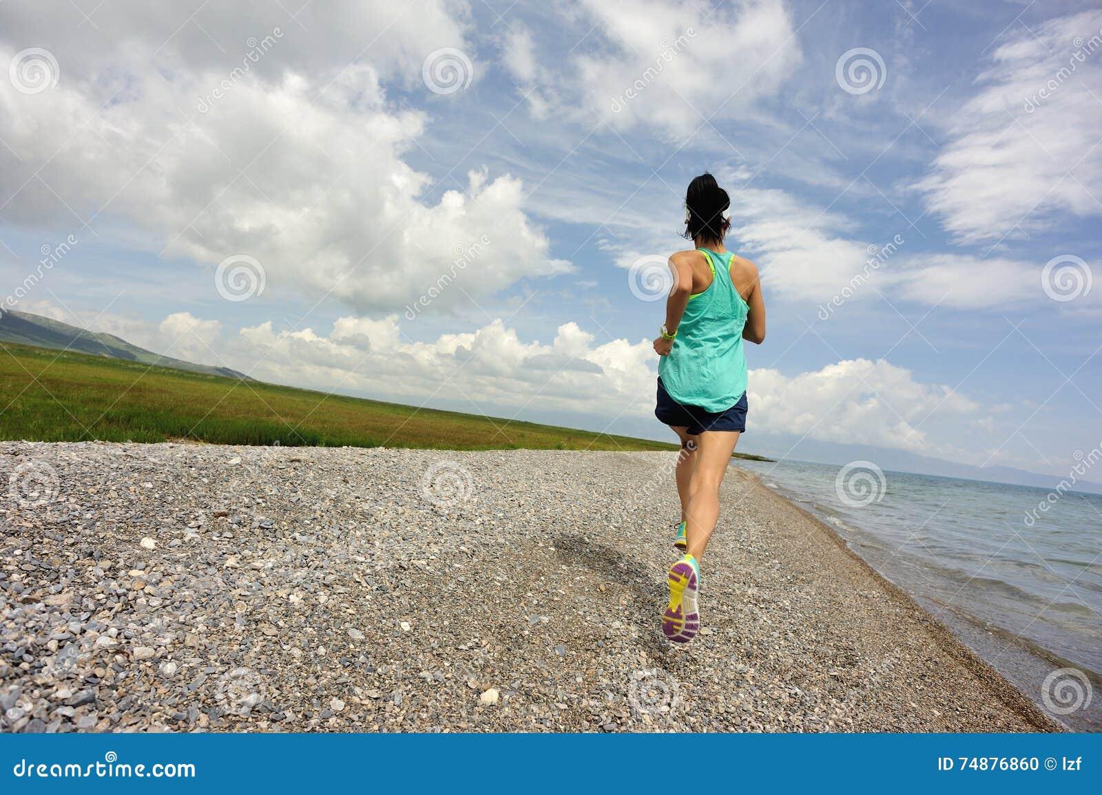 健身妇女运行在海边的足迹赛跑者