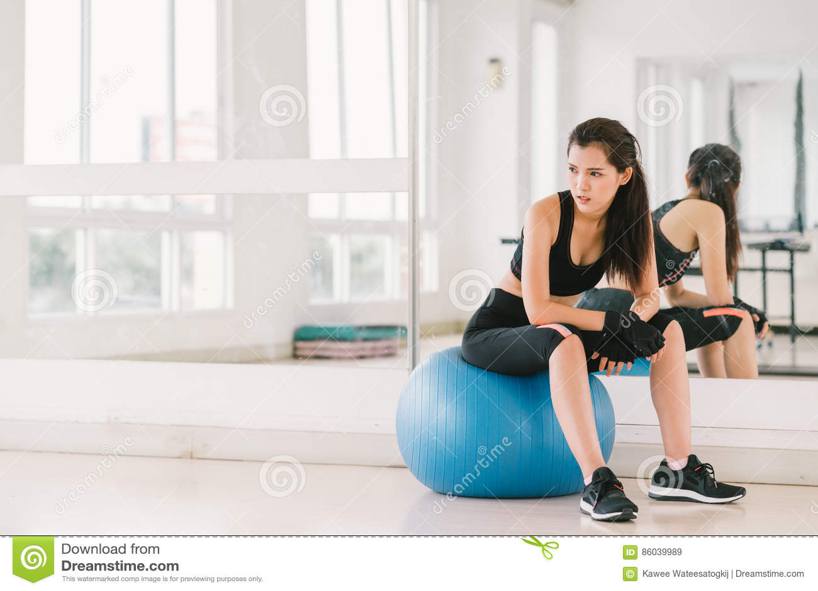 健身球的年轻和坚定的性感的亚裔女孩在与拷贝空间、体育和健康生活方式概念的健身房
