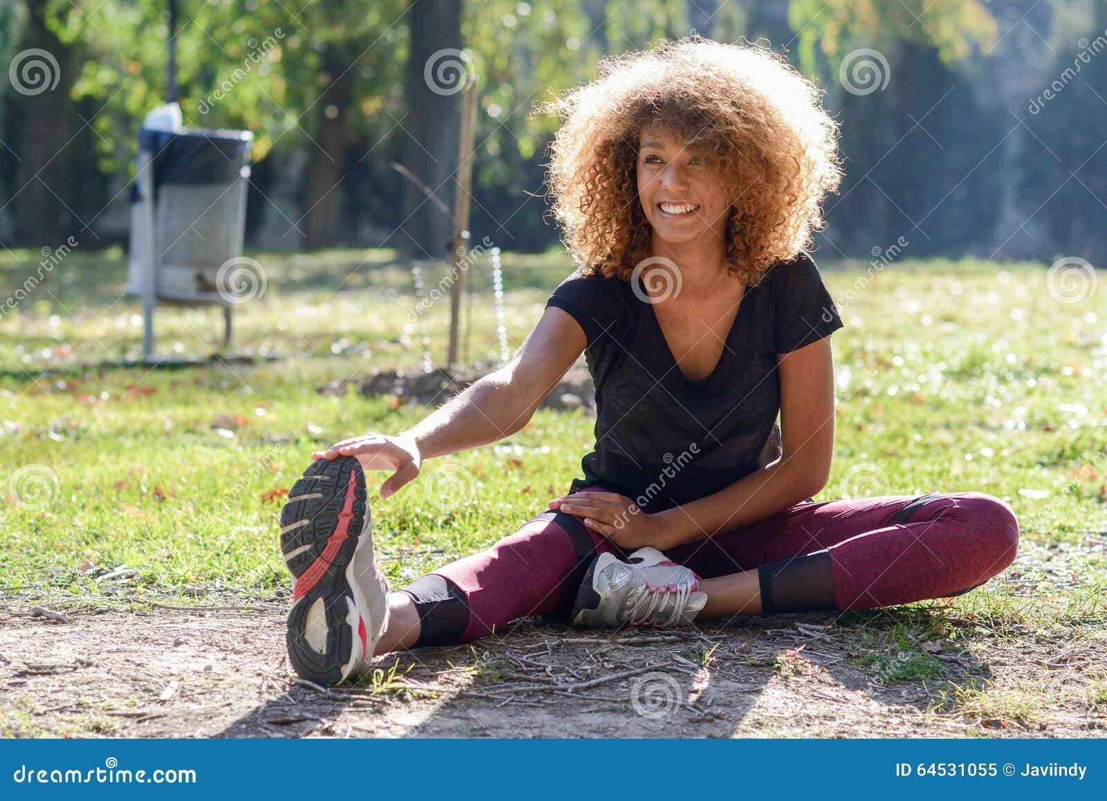 健身舒展腿的黑人妇女赛跑者在奔跑以后