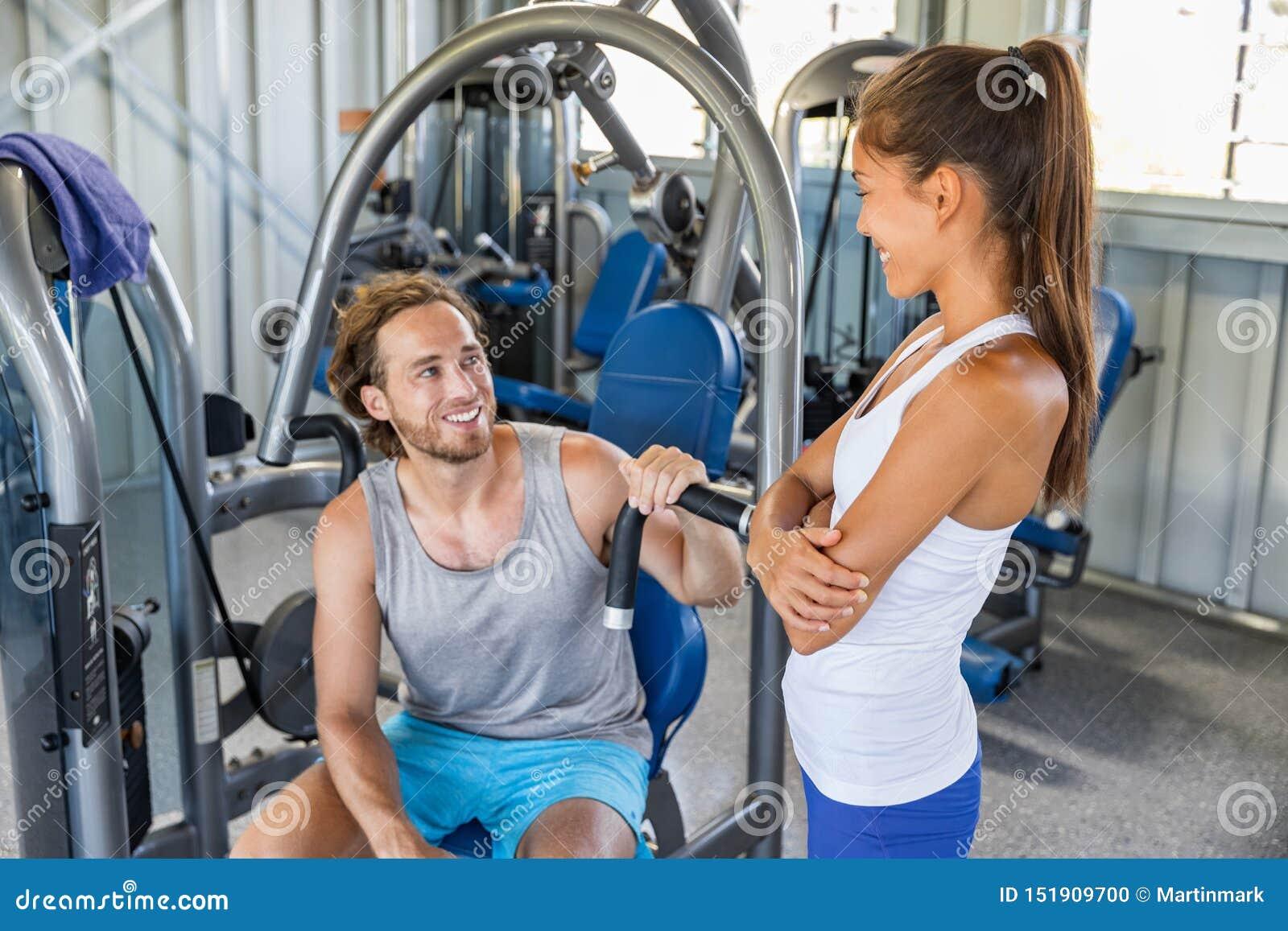 健身谈话健身房的教练员供以人员在锻炼设备机器的训练户内 结合愉快解决