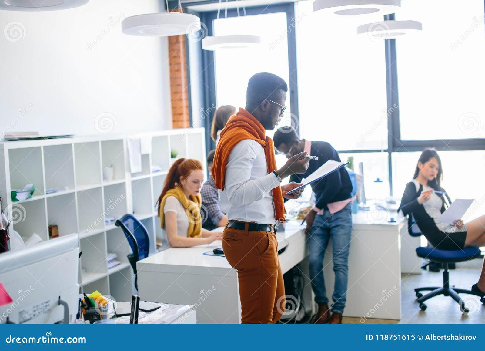 偶然成套装备的年轻精力充沛的办公室工作者读重要纸的