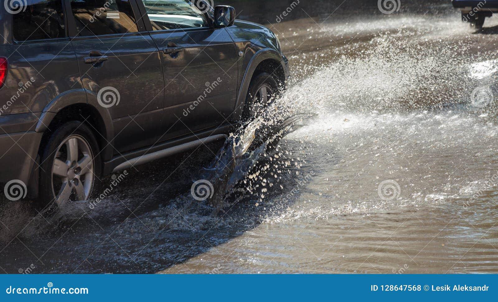 傲德萨,乌克兰2018年7月-3 :驾驶在一条被充斥的路的汽车在雨造成的洪水期间猛冲 在水的汽车浮游物,充斥st