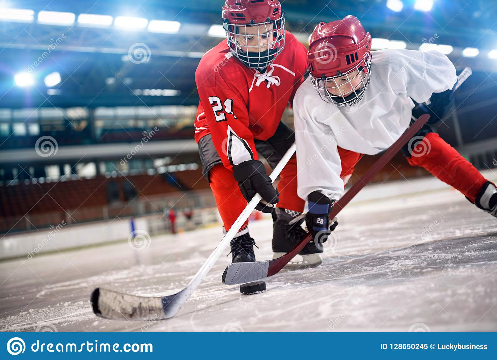 儿童处理在冰的曲棍球运动员顽童