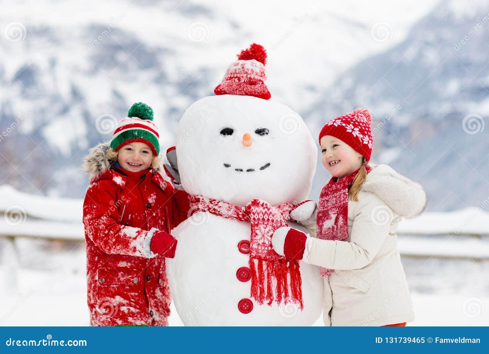 儿童大厦雪人 孩子修造雪人 使用户外在多雪的冬日的男孩和女孩 在圣诞节的室外家庭乐趣