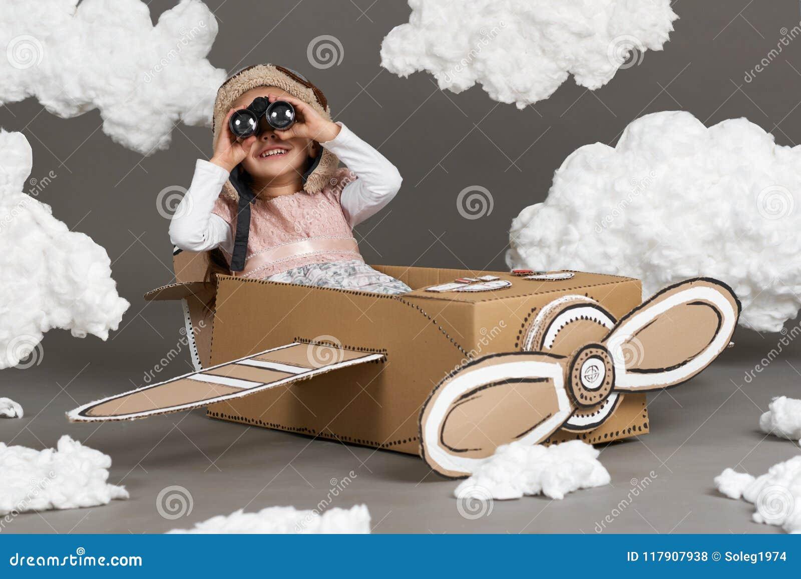 儿童女孩充当飞机由纸板箱和梦想成为做成飞行员,棉绒云彩在一灰色backgrou的